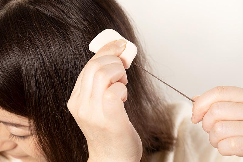 ファンデーションタイプの白髪隠しを塗る女性