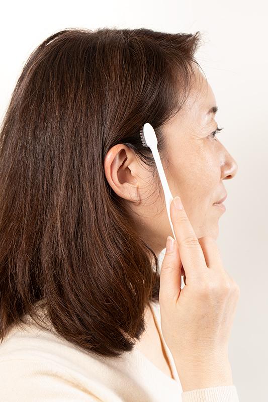 歯ブラシを使って白髪染めをする女性