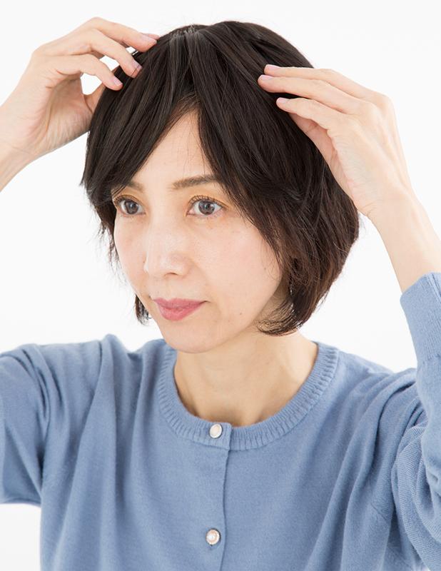 ウイッグを髪の毛にのせて調整している女性