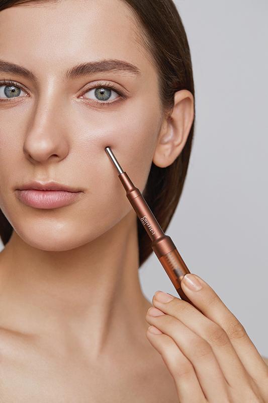 ペン型美顔器を頬に当てる外国人女性