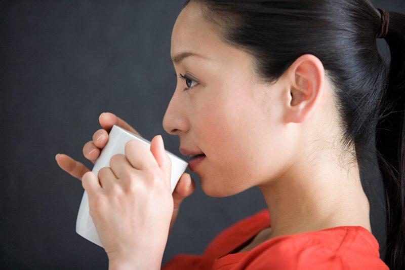 お茶を飲んでいる痩せた女性