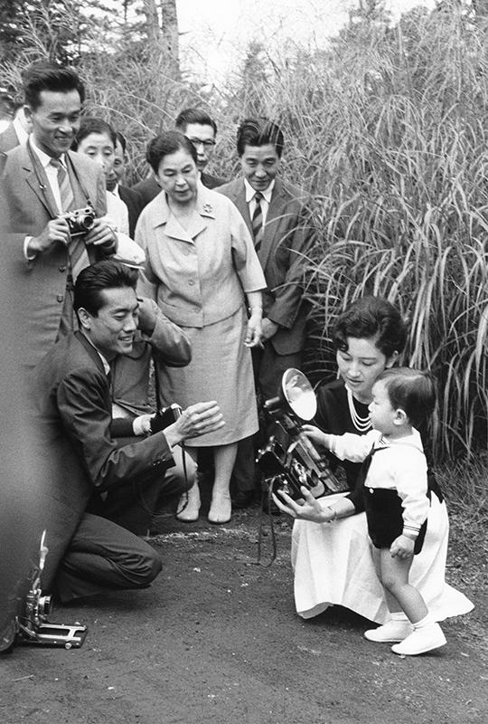 記者に囲まれ、大きなカメラを手にする幼いころの天皇陛下と見守る美智子さま