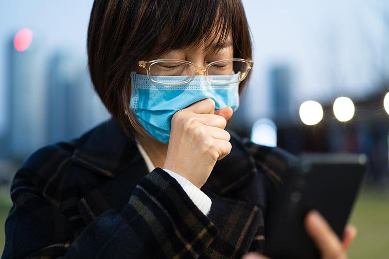 眼鏡をした女性がマスクをしてせき込んでいる