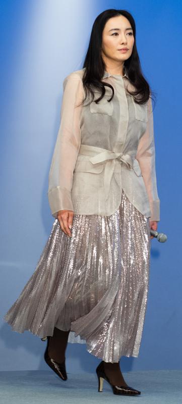 仲間由紀恵が透け間のあるグレーのジャケットにシルバーのプリーツスカートを着ている