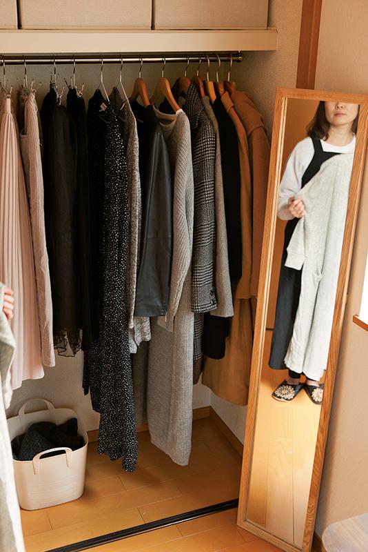 クローゼット前の鏡で洋服を着て思案している女性