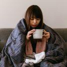 布団をかぶってスープを飲んでいる風邪を引いた女性