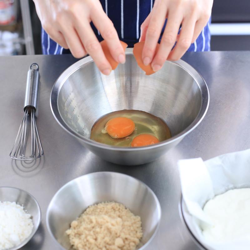 「水切りヨーグルトケーキ」の材料。卵を割っている