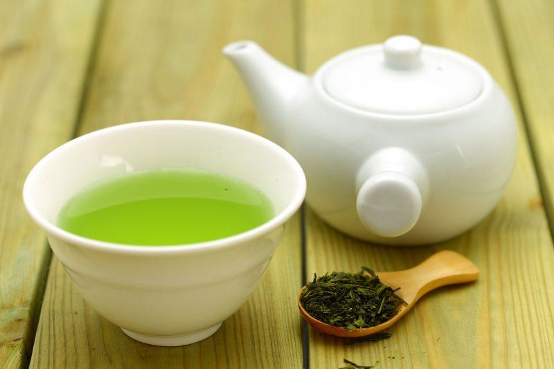 緑茶と急須、お茶の葉がテーブルに並んでいる