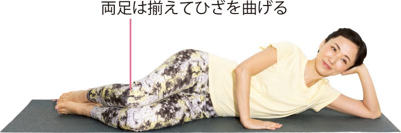 横向きに寝て、下側の腕で頭を支え、上側の腕は胸の前につく。両足は揃えて、ひざを曲げている女性
