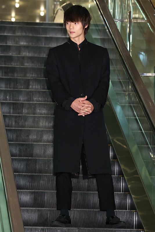 エスカレーターをバックに、全身黒のスタイルでかっこよく佇む窪田正孝