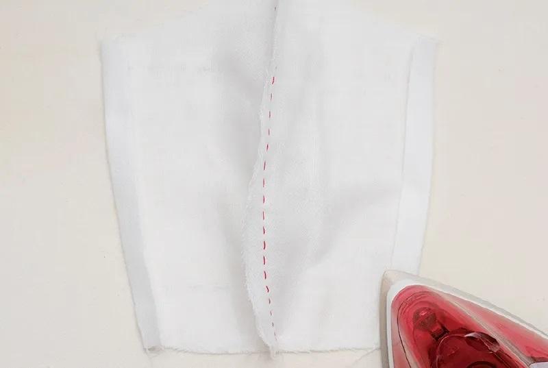 布マスクの内側ガーゼを開いて両端1㎝を折り、アイロンをあてる画像