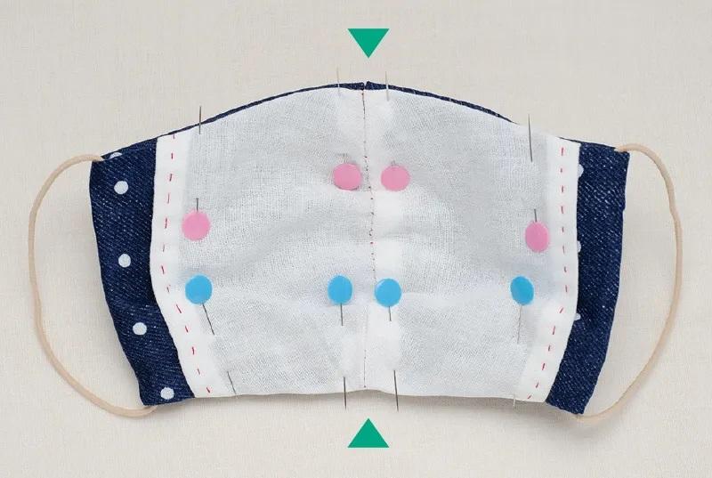 水玉柄布マスクの内側にポケットになるガーゼを当て、ポケットと本体の中心の位置を合わせて、まち針で押さえた画像