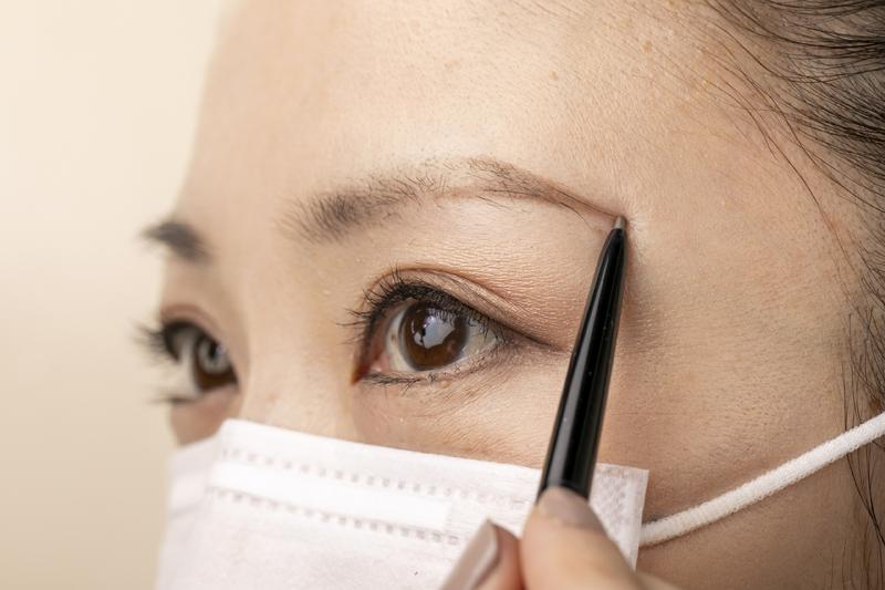 ペンシルで眉尻を描くマスクをした女性