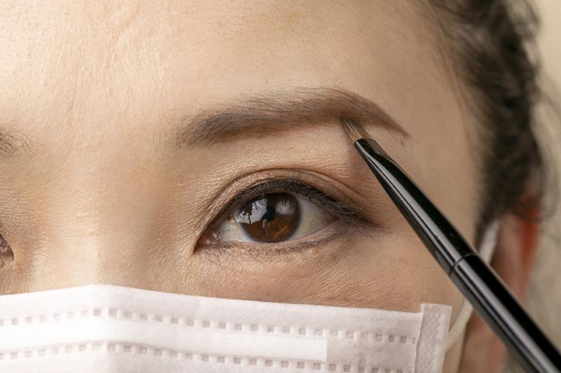 パウダーを使って眉の下を描くマスクをした女性の画像