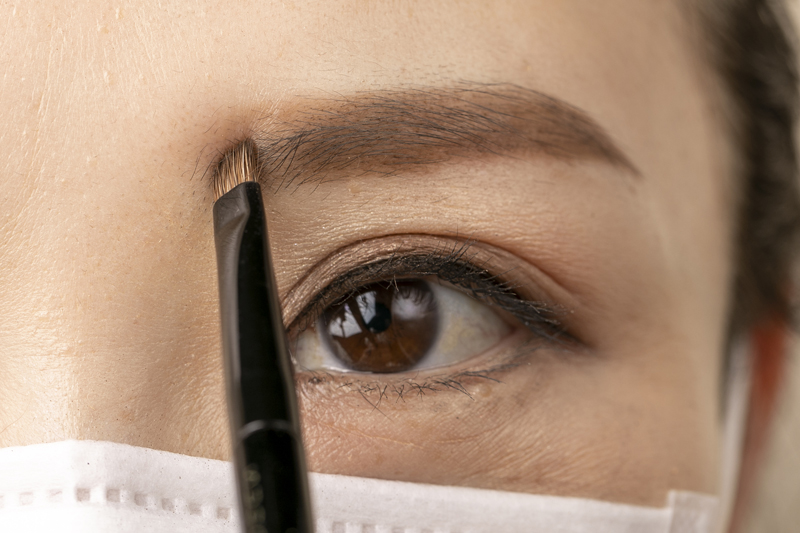 眉頭に眉ブラシを当てたマスクをした女性の目元画像