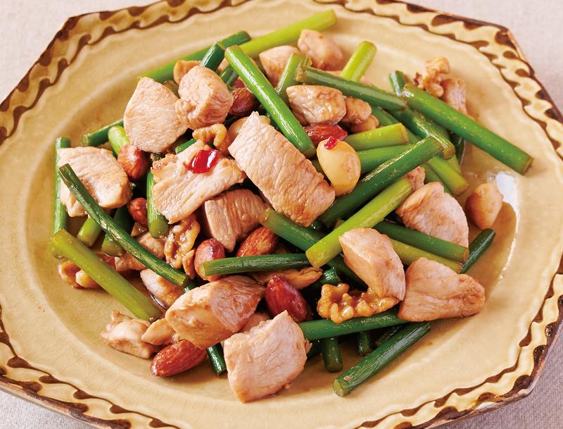 鶏肉とにんにくの芽とナッツのピリ辛炒めが器に盛り付けられている