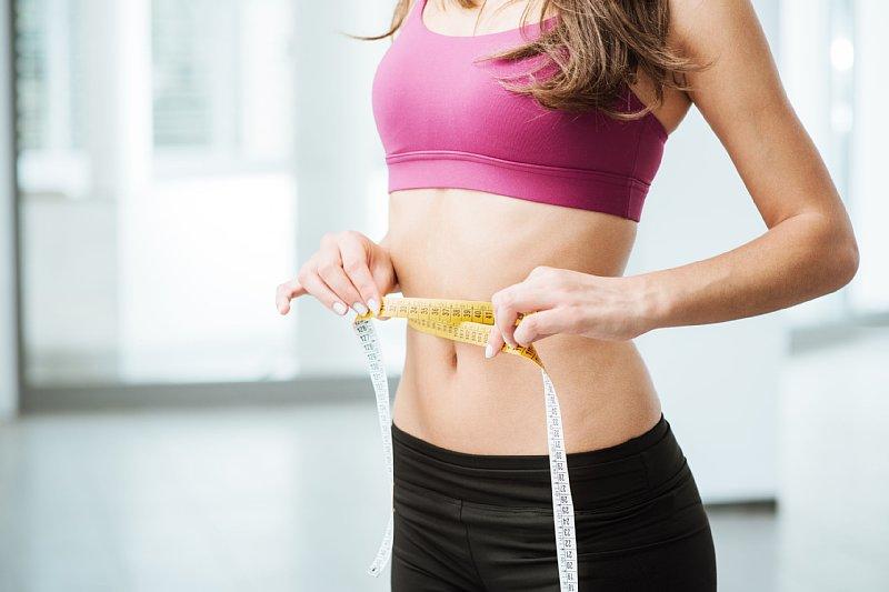 メジャーでお腹周りを計測している女性のお腹