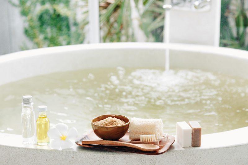 お湯をためている大きなお風呂とフチに乗せたオイルやせっけん、タオル