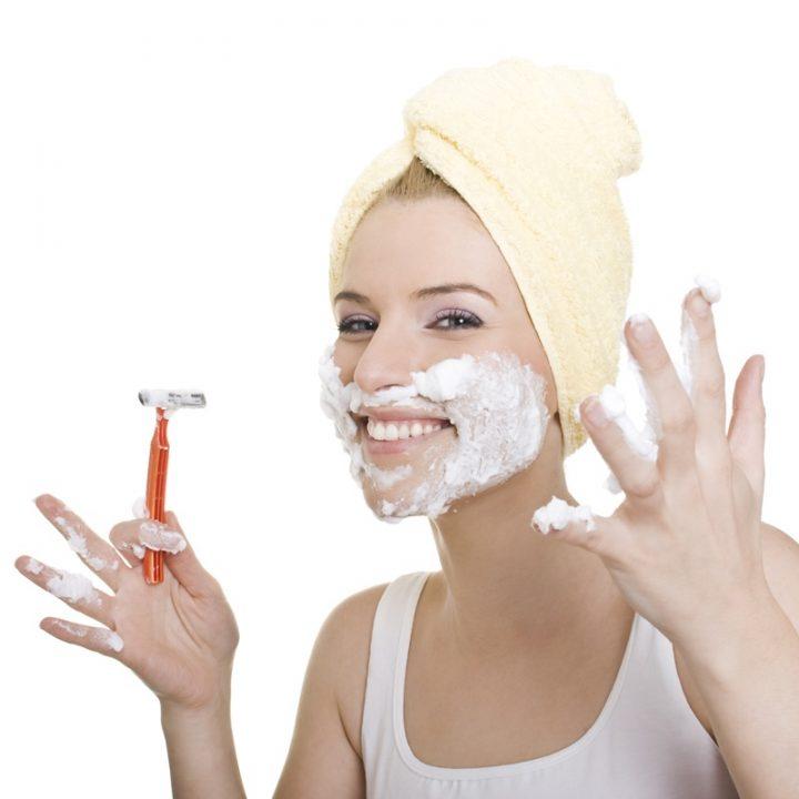 顔に泡をつけ、カミソリを持っている女性