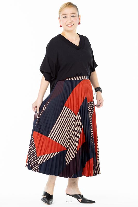 黒のVネックカットソーにプリーツスカートを合わせた女性