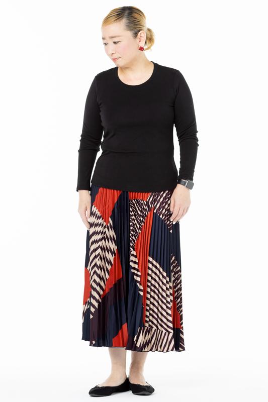 黒の丸首カットソーにプリーツスカートを合わせた女性