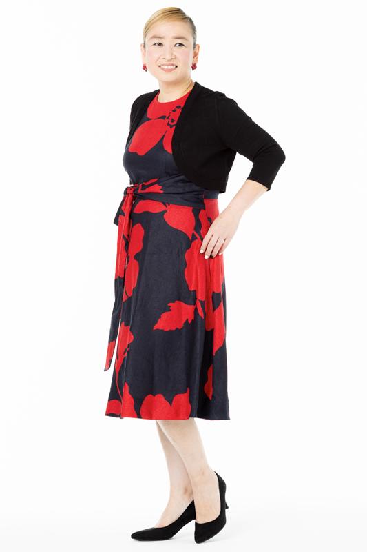 黒に赤い大柄の花が入ったワンピースを着た女性