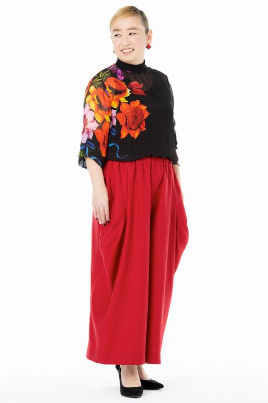 黒のデザインカットソーに赤いパンツを着た女性
