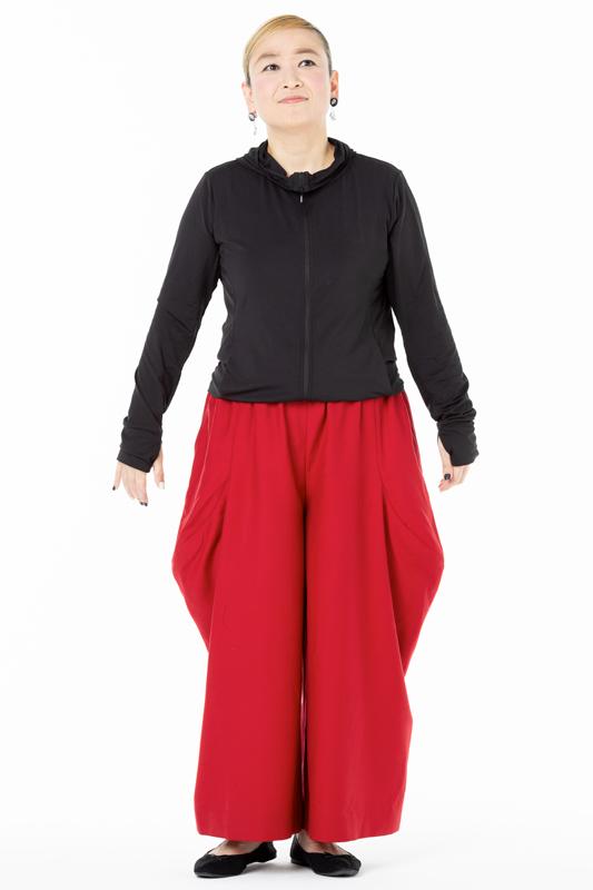 ゆったりとした黒無地のカットソーに赤いパンツを着た女性