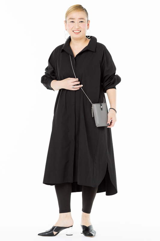 黒のシャツワンピースを着てグレーのポシェットをさげた女性