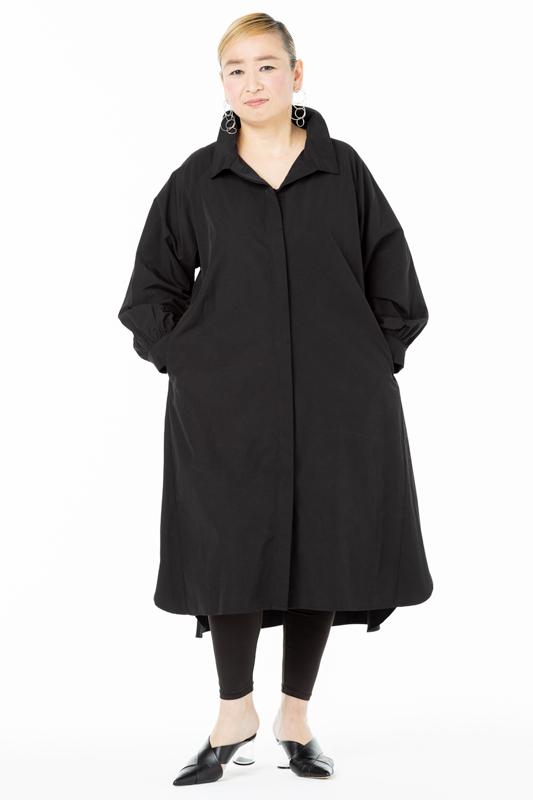 ゆったりとした黒のシャツワンピースを着た女性