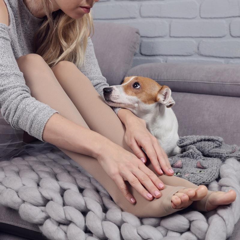 体育座りをする女性とその足元にいる犬