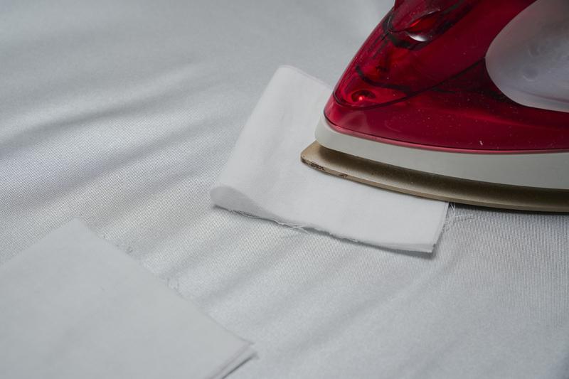ポケット用生地を半分に折り、アイロンをかけている画像