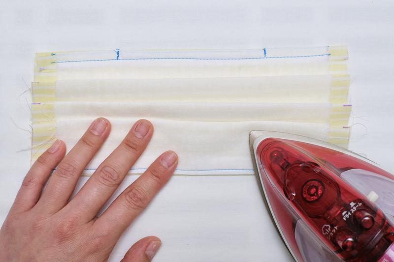 布を上から谷折り、山折りしプリーツを作り、アイロンで折り目をつけている画像