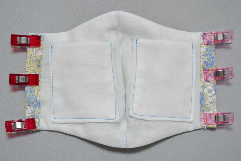 ポケット付きマスクの内側を表にし、両端をクリップで留めた画像