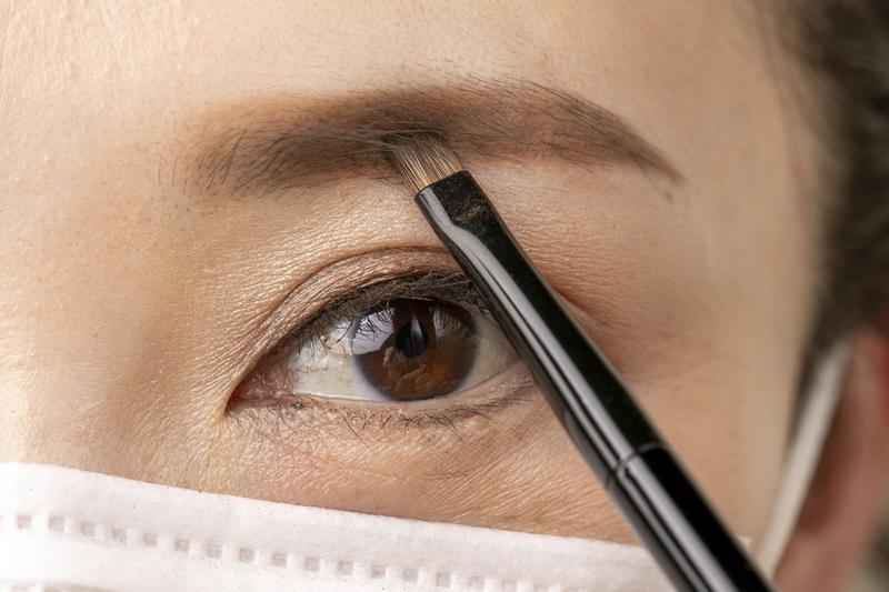 眉の黒目の上の部分にパウダーを重ねるマスク女性の目元画像