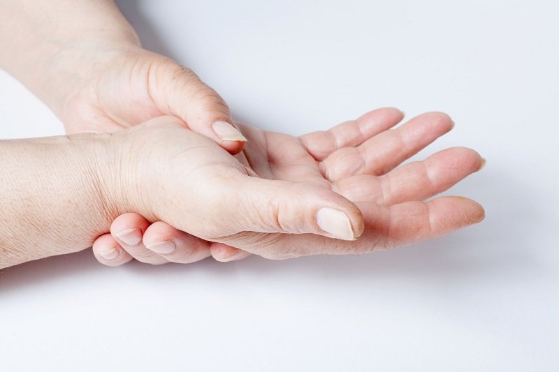 手の平をもう片方の手で押さえる女性の手の画像