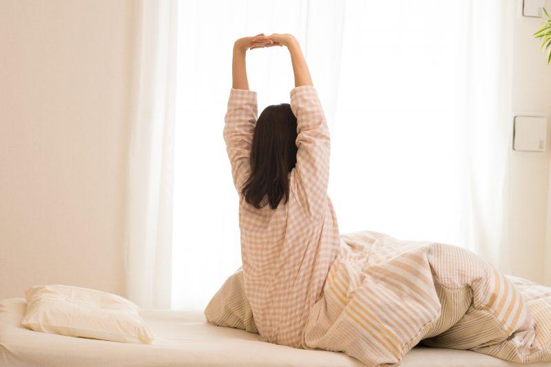 ベッドから起き上がり伸びをする女性
