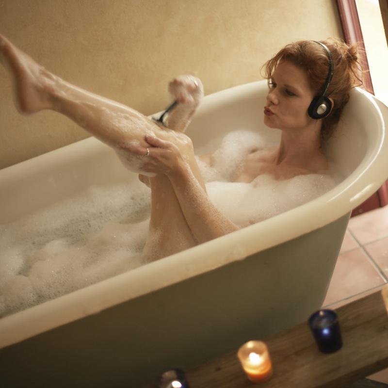 バスタブで足の毛を剃る女性