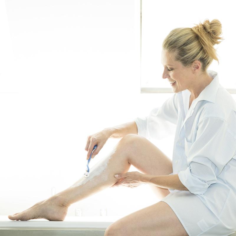足の毛を剃る女性