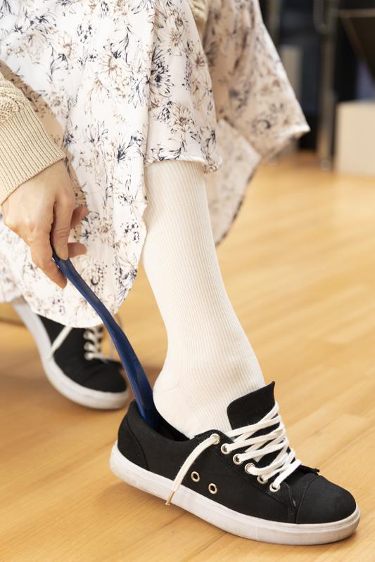 靴べらをつかって靴を履いている