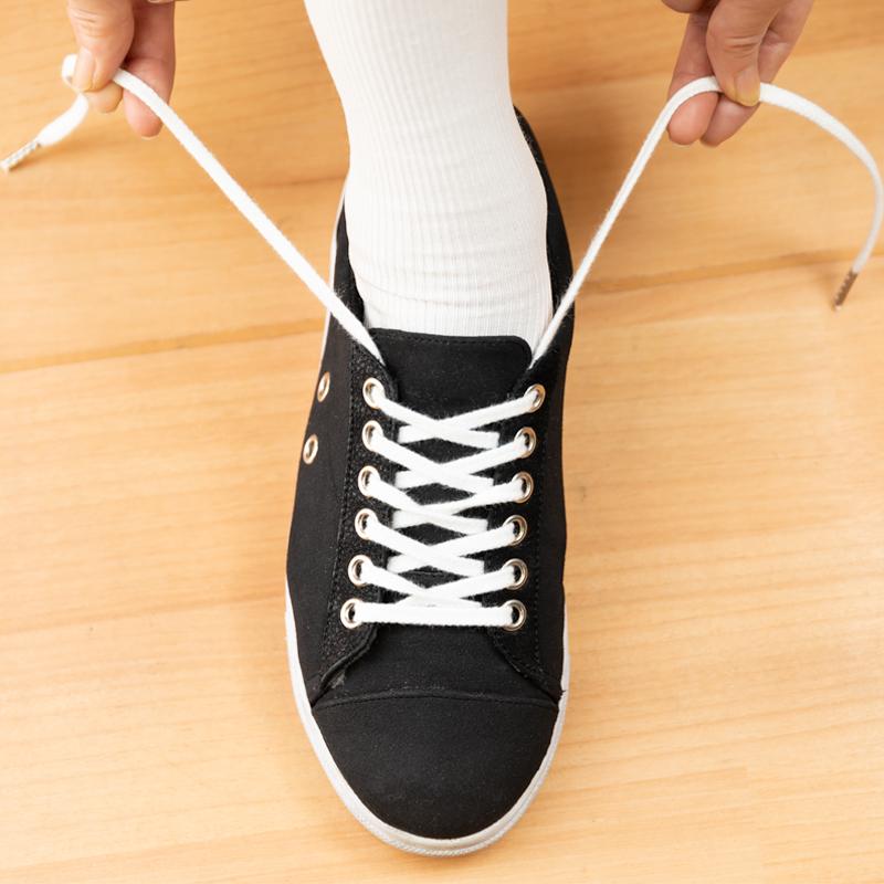 一番上のハトメの下からひもを出して靴を履いている