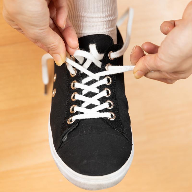 靴ひもを下から引っ張りながら履いている