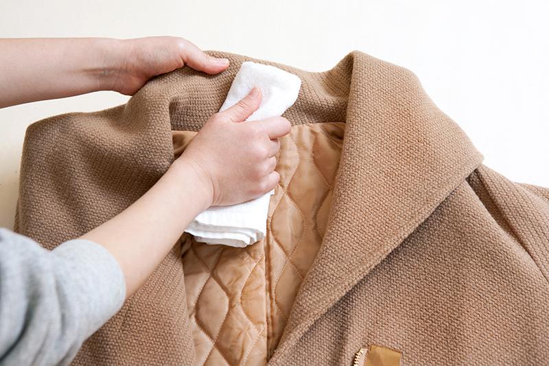 コートの襟元を布で拭いている