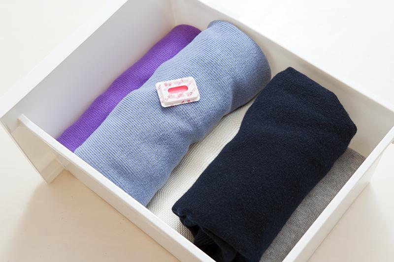 衣装ケースにまとめたセーターを防虫剤とともにしまっている