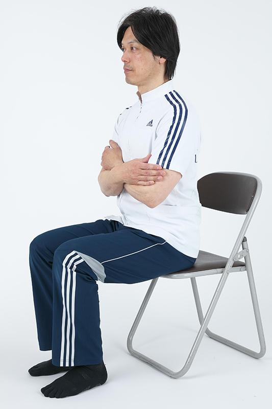 椅子に座って腕を組んで上体を起こしている