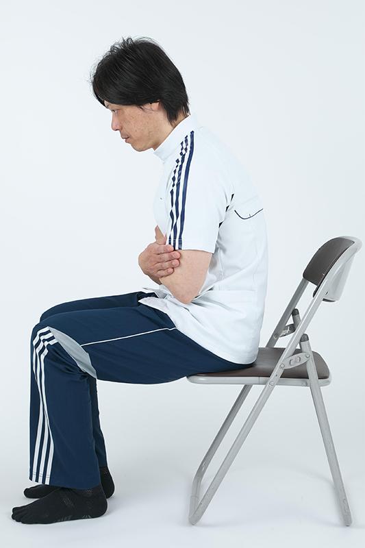 背中を丸めて椅子に座って運動をしている