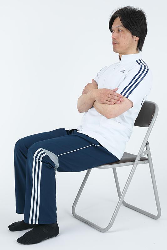椅子の背もたれに向かって上体を倒している