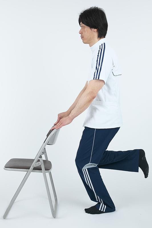 椅子の背もたれに手を添えて立って片足を深く曲げている