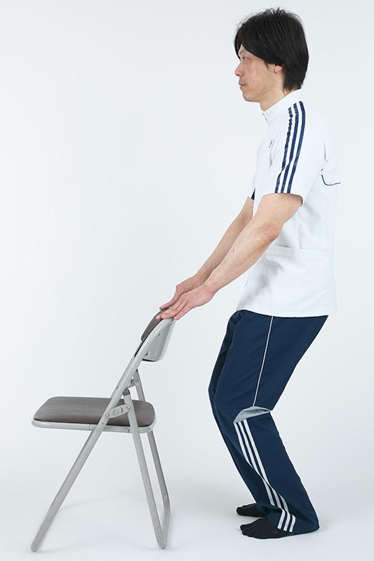 椅子の背もたれに手を添えて立って両ひざを曲げている