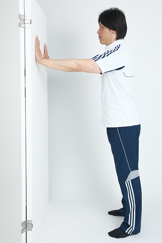 壁から1mほど離れて立ち、手は肩幅より少し広げて壁についている